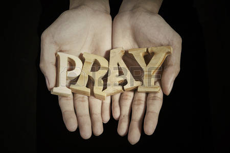 54428235-close-up-of-prayer-hands-showing-a-word-of-pray-in-dark-background